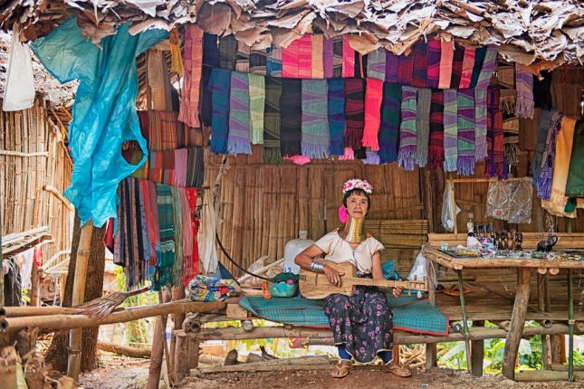A Long neck woman sell handicraft, and play guitar